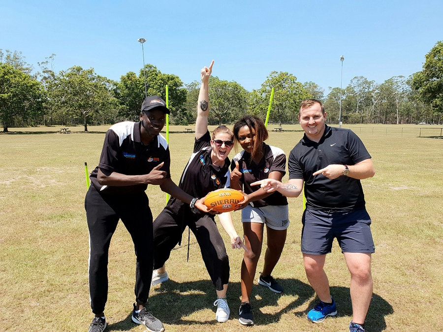 Four people in a sports field holding a AFL football.
