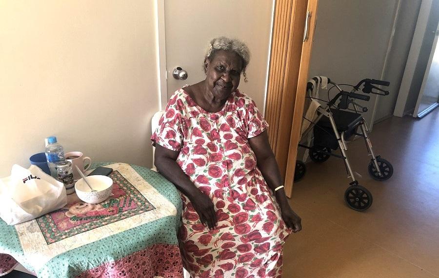 Naika sitting in her Seniors accommodation, smiling.