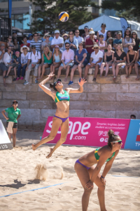 Two women playing volleyball